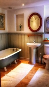 private bathroom with shower and cast iron bath tub